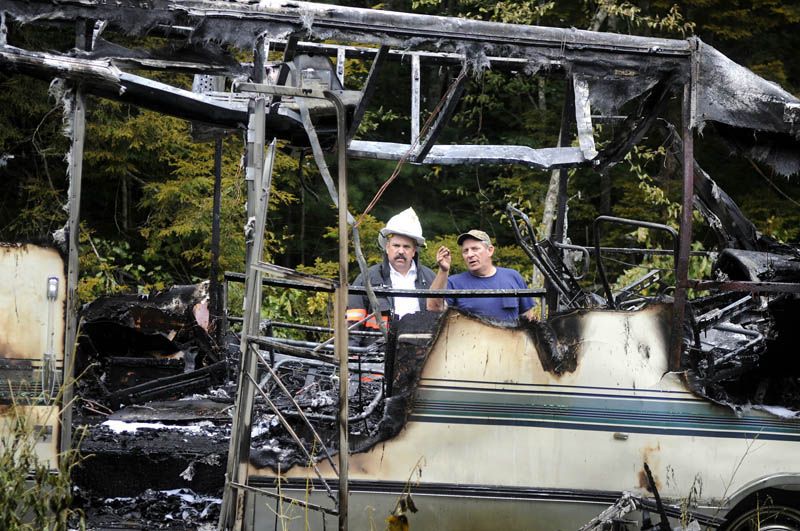 IMMOBILE: Richard Hutchings, right, assesses the smoldering frame of his recreational vehicle Thursday with Gardiner Fire Chief Mike Minkowsky after a blaze outside Hutchings' Gardiner home destroyed the vehicle. No injuries were reported, according to firefighters.