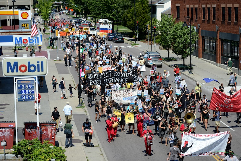 Hundreds of protesters march down South Winooski Avenue in Burlington, Vt., during demonstrations on Sunday, July 29, 2012, as the 36th Annual Conference of New England Governors and Eastern Canadian Premiers set up at the hotel.