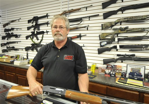 Randy Hodges displays a firearm at the Gun Vault in High Point, N.C., on Monday. Gun sales have jumped after the mass shooting last week in Colorado. (AP Photo / Sonny Hedgecock)