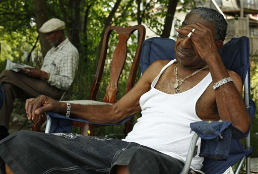 Men who identified themselves as Papa B, left, and Cadillac Bob, find refuge from the heat in a shaded lot between their homes on Thursday on Chicago's south side. Chicago hit 103 degrees.