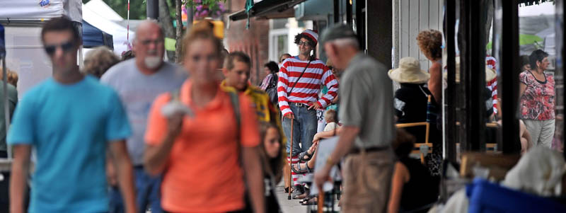 "David Gulak, center, dressed as Waldo, from the popular children's book series, ""Where's Waldo?"" is spotted at the Waterville Intown Arts Festival on Main Street on Saturday."