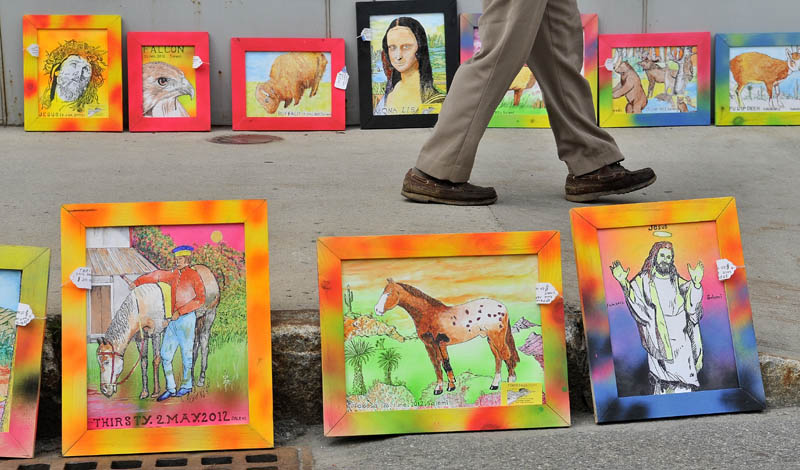 The art work of John Salemi lines the side walk on Main Street in downtown Waterville during the Intown Arts Festival on Saturday.