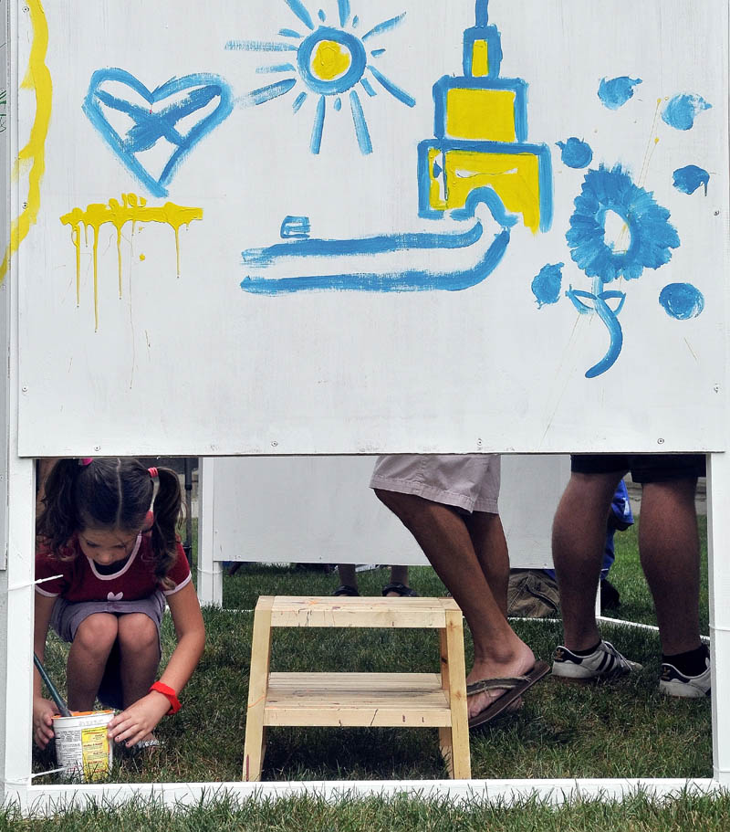 Addison Lopes, 6, grabs paint and a brush as she adds her artistic impression to the wall provided by Common Street Arts in Castonguay Square during the Waterville Intown Arts Festival on Main Street on Saturday.