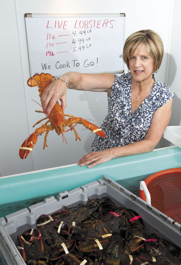 Paula Coppersmith holds a lobster at Dock's Seafood restaurant and market in South Portland, where they're selling five lobsters for $24. Many stores are selling the king of seafood for under $5 a pound, making it cheaper than bologna by weight.