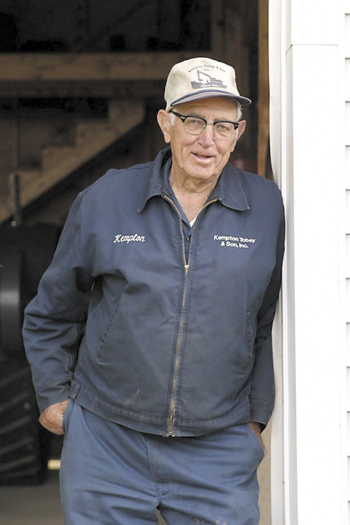 "Kempton Tobey leans against the door frame to his ""dream shop,"" which housed his grandfather's tractor, among other things."