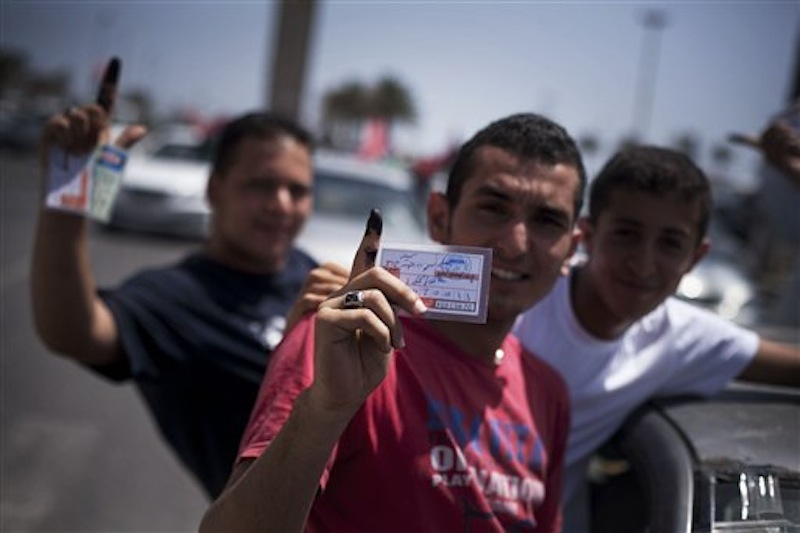 Libyan men hold their elections ID cards while celebrating election day in Tripoli, Libya, Saturday, July 7, 2012. Jubilant Libyan voters marked a major step toward democracy after decades of erratic one-man rule, casting their ballots Saturday in the first parliamentary election after last year's overthrow and killing of longtime leader Moammar Gadhafi. But the joy was tempered by boycott calls, the burning of ballots and other violence in the country's restive east. (AP Photo/Manu Brabo)
