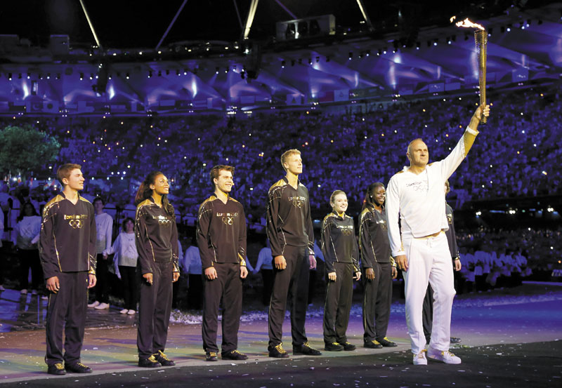 Olympic gold medalist Sir Steve Redgrave, right, holds the Olympic torch after entering the stadium during the opening ceremony at the 2012 Summer Olympics on Saturday in London. Redgrave handed the flame off to the young athletes behind him, who in turn lit the Olympic cauldron.