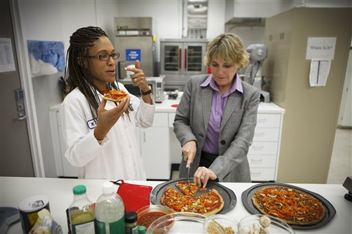 NASA's Advanced Food Technology Project manager Michele Perchonok, right, and Lockeed Martin Sr. Research Scientist Maya Cooper, try a pizza recipe in a test in a kitchen at Johnson Space Center in Houston on Tuesday.