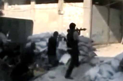 This image made from amateur video released by the Ugarit News and accessed Sunday, July 15, 2012, purports to show Free Syrian Army soldiers clashing with Syrian government forces in Damascus, Syria. Syrian troops and rebels clashed inside Damascus for a second day on Monday, causing plumes of black smoke to drift over the city's skyline in some of the worst violence in the tightly controlled capital since the country's crisis began 16 months ago.