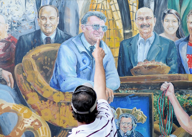 A visitor points to the spot in a mural where a halo that was above the late Penn State football coach Joe Paterno has been painted over by the artist in State College, Pa. on Saturday.