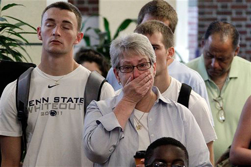 Susan DelPonte, center, of State College, Pa., reacts to a television in the HUB on the Penn State University main campus in State College as the NCAA sanctions against the Penn State University football program were announced Monday.