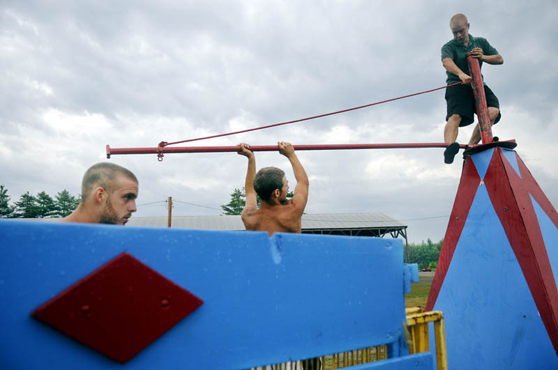 GOING UP: Carnival workers with Kavanaugh Amusements assemble a ride Tuesday at the Pittston Fair ahead of an approaching thunderstorm. The annual agricultural exhibit commences Thursday and runs through Sunday