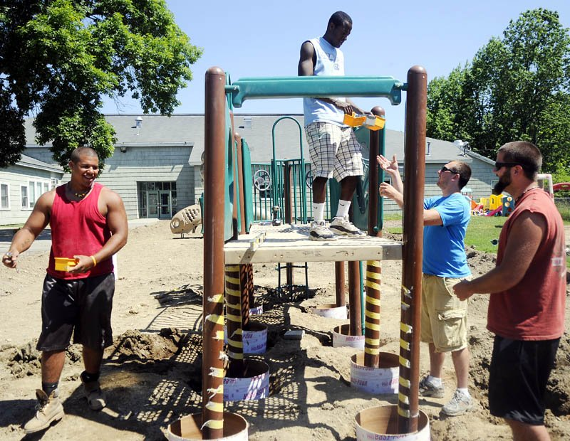 Eddie Donnell, left, Tookie Amosun, Cody Peckham and Ethan Stanchfield assemble a new playground Tuesday at the Boys and Girls Club in Gardiner. The Club spent four years raising funds for the playground.