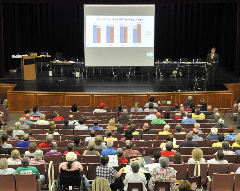 Residents of Regional School Unit 18 listen to superintendent Gary Smith, top right, make a presentation on the school budget at Messalonskee High School in Oakland on Thursday.