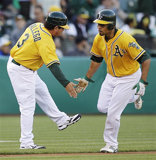 Oakland Athletics' Coco Crisp, right, is congratulated by third base coach Mike Gallego (3) after Crisp hit a home run off Boston Red Sox's Jon Lester in the first inning of a baseball game, Tuesday, July 3, 2012, in Oakland, Calif. (AP Photo/Ben Margot)