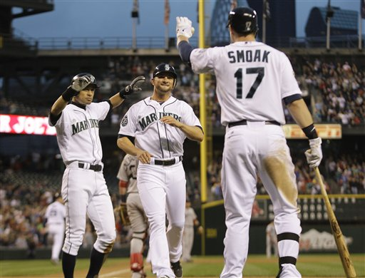 Seattle Mariners' Casper Wells, center, and Ichiro Suzuki, left, are greeted by Mariners' Justin Smoak as they score in the sixth inning of a baseball game, Saturday, June 30, 2012, in Seattle. (AP Photo/Ted S. Warren)