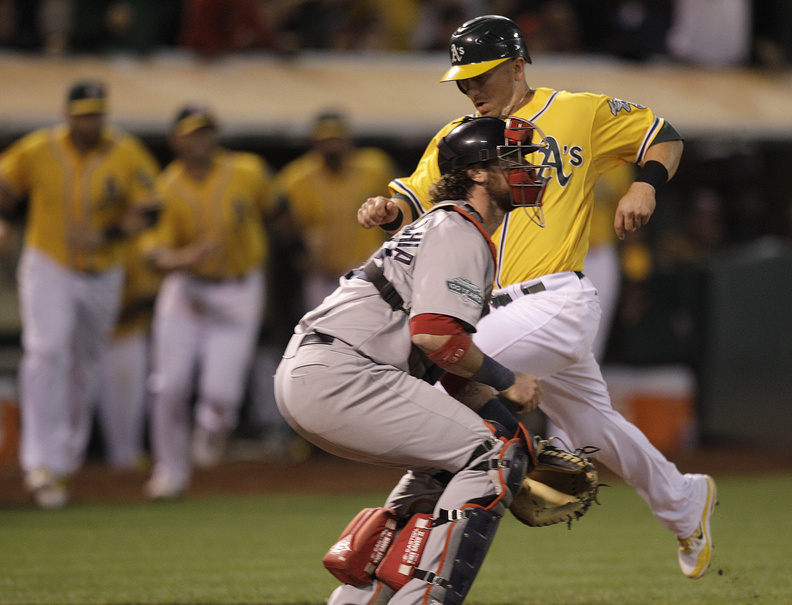 Oakland Athletics' Cliff Pennington, right, scores the game- winning run while Boston Red Sox catcher Jarrod Saltalamacchia waits for the ball in the ninth inning Tuesday in Oakland, Calif. Pennington scored on a sacrifice fly hit by Coco Crisp.