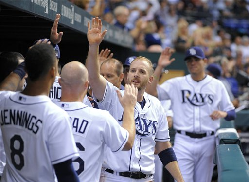 Tampa Bay Rays' Jeff Keppinger, center, celebrates with teammates in the dugout after scoring on a sacrifice fly by Elliot Johnson during the seventh inning of a baseball game against the Boston Red Sox on Saturday, July 14, 2012, in St. Petersburg, Fla. (AP Photo/Brian Blanco)