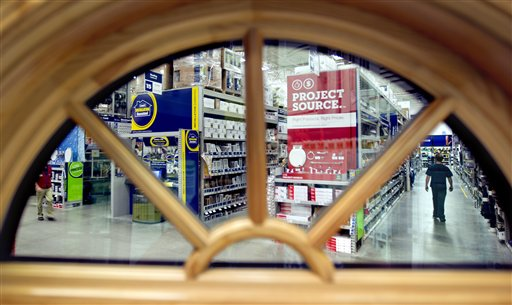 A shopper is seen through a window on display at a Lowe's store in Atlanta. Americans cut their spending at retail businesses for a third straight month, as a weak job market made consumers more cautious.