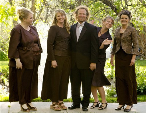 """In this undated file photo provided by TLC, Kody Brown, center, poses with his wives, from left, Janelle, Christine, Meri, and Robyn in a promotional photo for TLC's reality TV show, """"Sister Wives."""" A Utah county attorney says he will not pursue criminal charges against this polygamous family made famous by a reality TV show. A federal judge is set to decide whether to allow a lawsuit to move forward that challenges the constitutionality of Utah's bigamy law."""