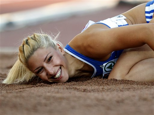 Greece's Voula Papachristou lands in the sand after her jump at the Women's Triple Jump final at the European Athletics Championships in Helsinki, Finland in June. The Hellenic Olympic Committee has removed Papachristou from Greece's 2012 Olympic team over comments she made on twitter making fun of African immigrants and expressing support for a far-right party. For better and for worse, the 2012 Olympics are being shaped, shaken and indisputably changed by social media sites such as Twitter, whose immediacy and public nature has added a new and chaotic element to the Games. The Associated Press photo