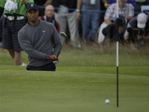Tiger Woods of the United States watches his chip shot out of the bunker on the 18th green to go on to drop into the hole at Royal Lytham & St Annes golf club during the second round of the British Open Golf Championship, Lytham St Annes, England, Friday, July 20, 2012. (AP Photo/Chris Carlson)