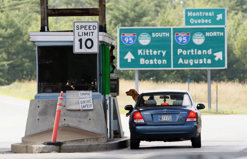 A motorist and her dog wait for change at a toll booth, Thursday, July 19, 2012, in Biddeford. The Maine Turnpike Authority may scale back its proposed toll increase. (AP Photo/Robert F. Bukaty)