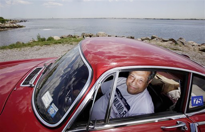 Irv Gordon poses for a picture in his Volvo P1800 in Babylon, N.Y., last week.