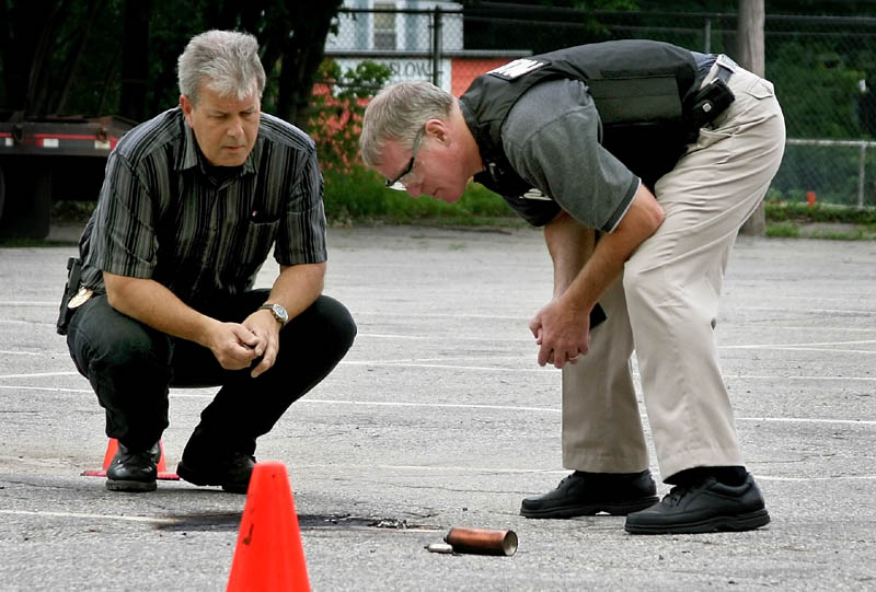 Staff photo by Ben McCanna Winslow Police Chief Jeffrey Fenlason, left, and State Fire Marshal supervisor Ken Grimes examine the remains of an exploded device in the Winslow Junior High Schooll parking lot Thursday. It was the third device exploded in Winslow in the last three days.