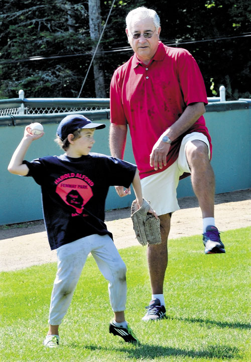 DO IT LIKE THIS: Former Major League baseball player Mike Torrez teaches Max Olmstead to step up when throwing during a baseball camp Monday at Little Fenway Park in Oakland.