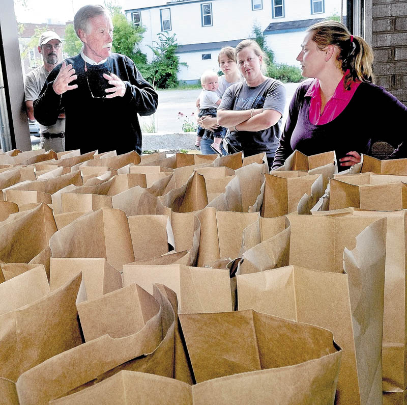 Former Maine governor and current U.S. Senate candidate Angus King speaks with Sarah Smith, right, and Amber Lambke beside bags of produce during a campaign tour stop at the Grist Mill in Skowhegan on Wednesday.