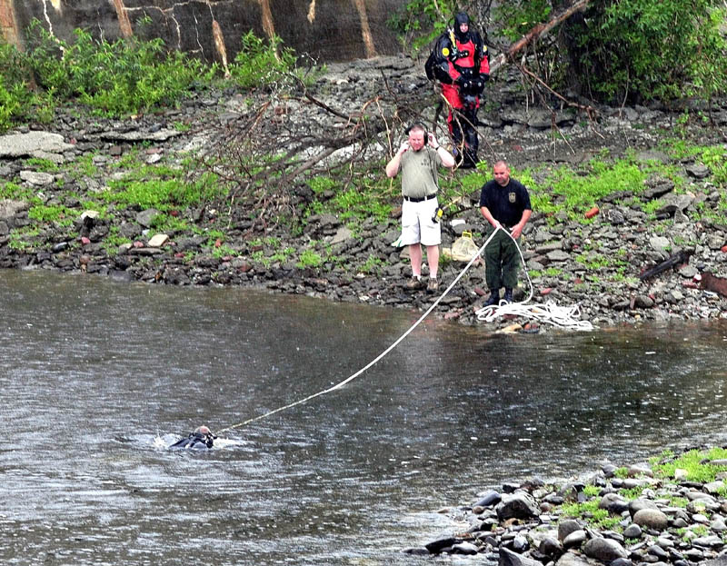Divers with the Maine State Police and Warden Service enter the Kennebec River below the Lockwood Dam in Waterville on Tuesday to search for missing toddler Ayla Reynolds.