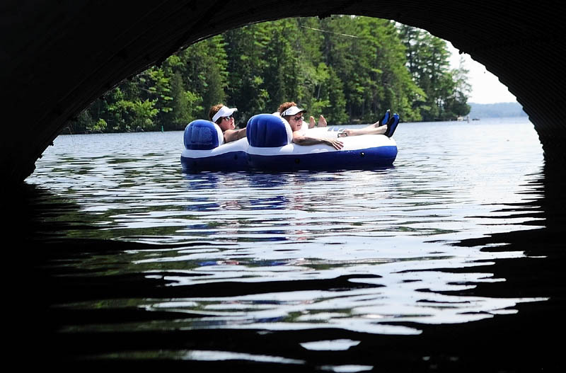 Carol Hummel, left, and Fran Mollis, both of New Jersey, drift past a culvert as they relax on a raft on a hot sunny Friday afternoon on Long Pond in Belgrade. The women said that this was the 36th summer that they'd been coming to Castle Island Camps and now they bring their children and grandchildren up for a week every summer.