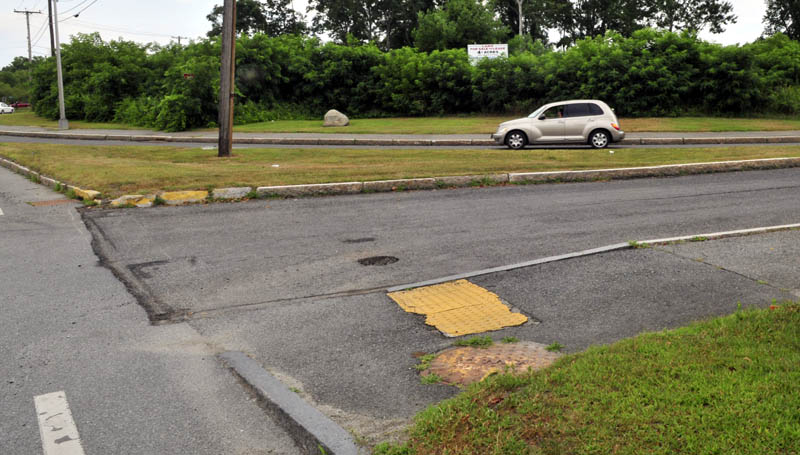 A motorist drives on Colby Circle where it intersects Front Street and College Avenue in Waterville near land where the new police station may be built. City councilors are also considering two other locations.