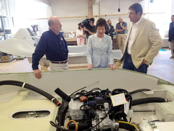 Flanked by David Packhem, president and CEO of Hodgdon Defense, left, and Tim Hodgdon, owner of Hodgdon Yachts, Sen. Susan Collins inspects the hull of the Greenough Advanced Rescue Craft during a tour of the facility in Bath today.