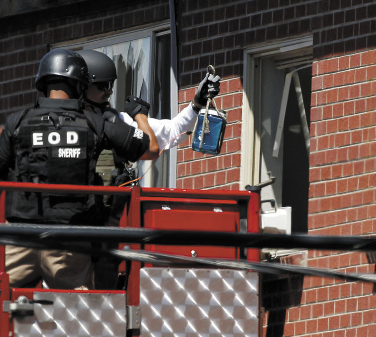 "Members of law enforcement wearing body armor and helmets prepare to what ATF sources describe as a""water shot"" in the apartment of alleged gunman James Holmes on Saturday in Aurora, Colo. The ""water shot"" is exploded and used to disrupt the device."