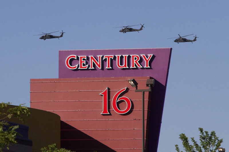 Three helicopters fly over the Century Theater on Saturday in Aurora, Colo.