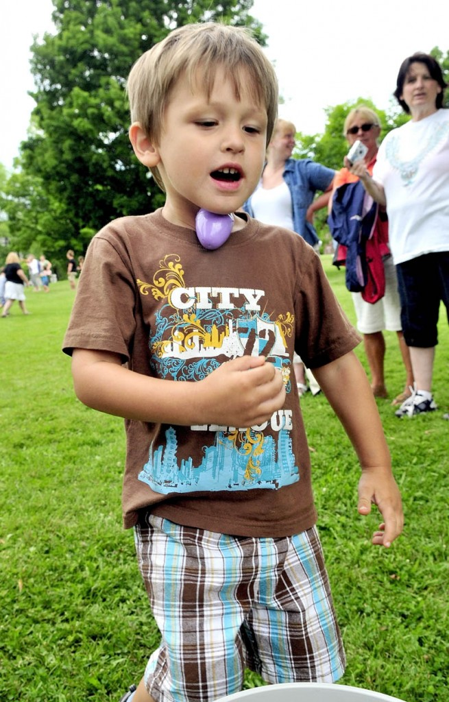 SCRAMBLED EGG: Dylan LaBelle runs with an egg under his chin in an event on Wednesday during the week-long Central Maine Egg Festival in Pittsfield.