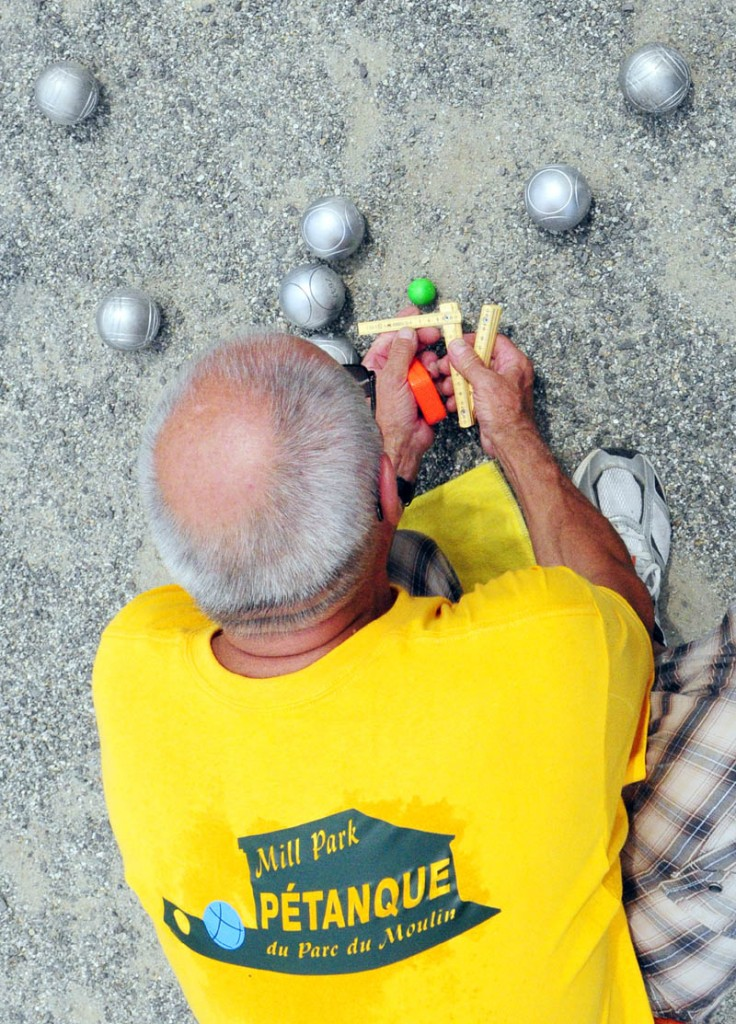Referee Michel Voyer, from Wissous, France, measures the distance between the green target ball, called a cochonnet, and the larger boules tossed by players to see which got closer during the Festival de la Bastille on Saturday afternoon in Augusta.