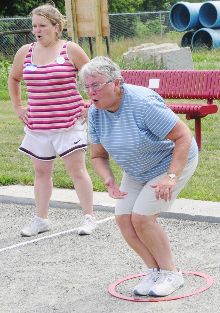 Erica Golden, left, and Cecile Gregoire react to Gregoire's shot during the petanque tournament held in Mill Park as part of the Festival de la Bastille on Saturday afternoon in Augusta.