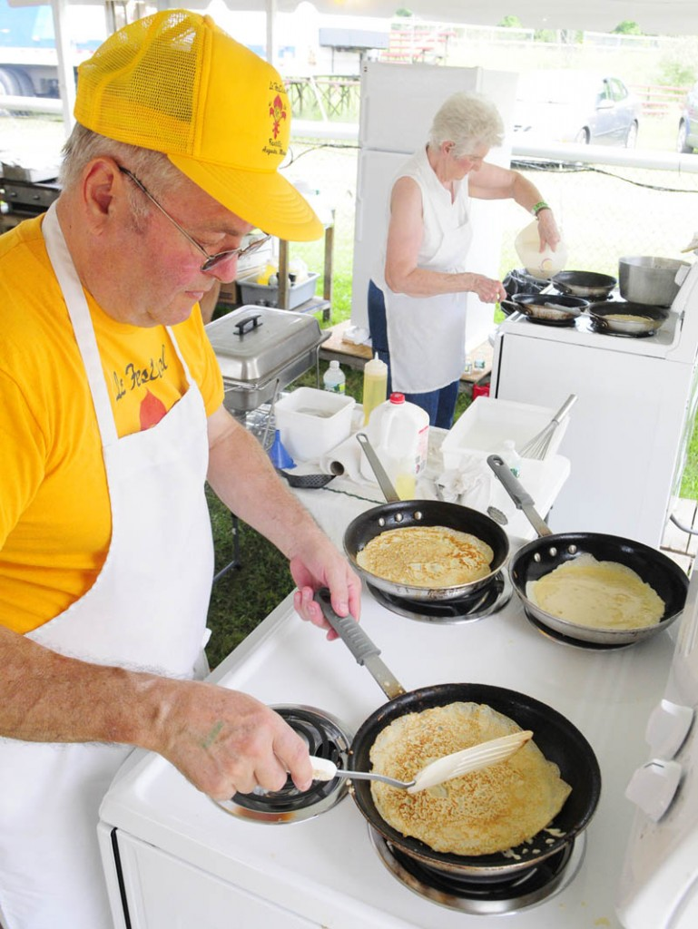 Norman Tondreau, left, and Gloria Morin cook crepes during the Festival de la Bastille on Saturday afternoon in Augusta. In addition to the thin French pancakes there were also boudin, meat and salmon pies, burgers and hot dogs. Today there will be a chicken barbecue from 11 a.m. to 1 p.m.