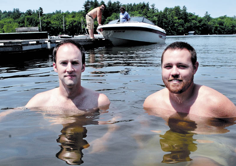"""IMMERSED IN THEIR WORK: Filmmakers Ryan Brod, left, and Daniel Sites are chest-deep in Great Pond in Belgrade on Sunday. They spent a lot of time there on the ice fishing documentary film """"Hardwater,"""" which will premiere at the Maine International Film Festival."""