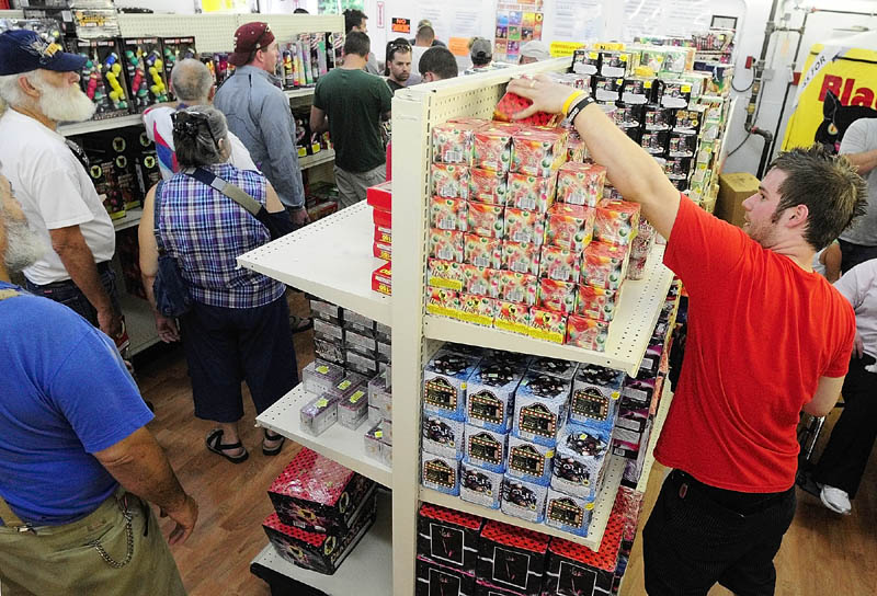 """Tyler Basinger, right, restocks shelves as customers line up to check out on Tuesday at the Pyro City fireworks store in Manchester. Scott Boucher, retail manager at the store, said there were people waiting out in the parking lot before they opened Tuesday. """"We're staying busy and everybody's happy,"""" he said. This was the first Independence Day since the state Legislature passed a law legalizing consumer fireworks last year."""