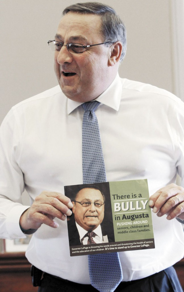 "In this Friday, April 27, 2012 photo, Gov. Paul LePage talks about his sense of humor while holding a poster that reads ""There is a bully in Augusta pushing around seniors, children and middle class families,"" during an interview with the Associated Press at his office at the State House in Augusta. Critics are putting pressure on LePage to apologize for referring to the Internal Revenue Service as ""the new Gestapo"" during his radio address Saturday."