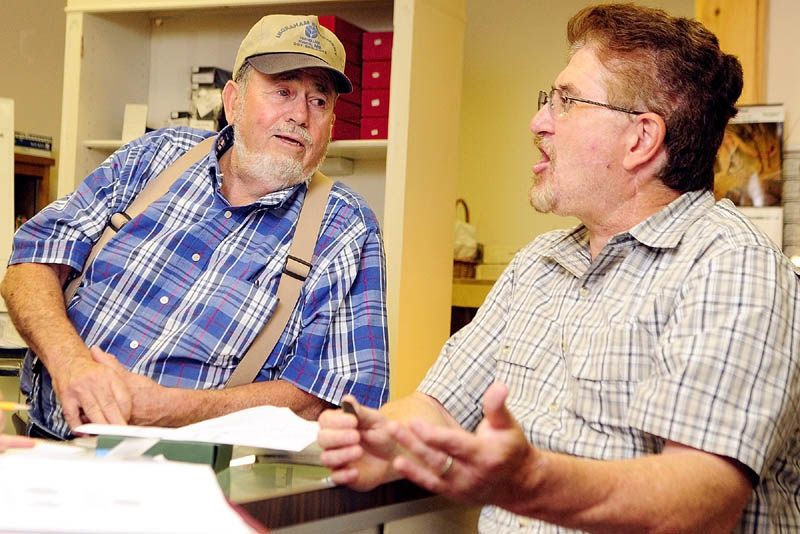 Thomas Donlon, left, and William Guerrette chat about the George Washington funeral medallion that Donlon recently bought on eBay on Thursday at China Lake Coins & Currency, at 285 State St., in Augusta.
