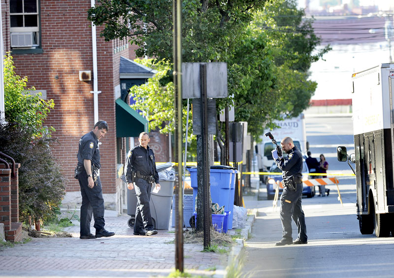 Portland police collect and photograph evidence at 105-107 India St., after an early-morning shooting in Portland.
