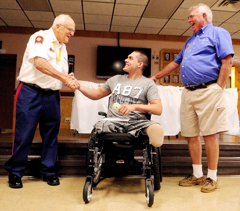 Jeremy Gilley, center, shakes hands with Marine Corps League Detachment No. 599 commandant Don Brawn, left, as Jerry Bechard, 1st Vice President of Le Club Calumet looks on at a fundraiser held on Wednesday night at Le Club Calumet in Augusta. Gilley received donations from the Marine Corps League and the Club.