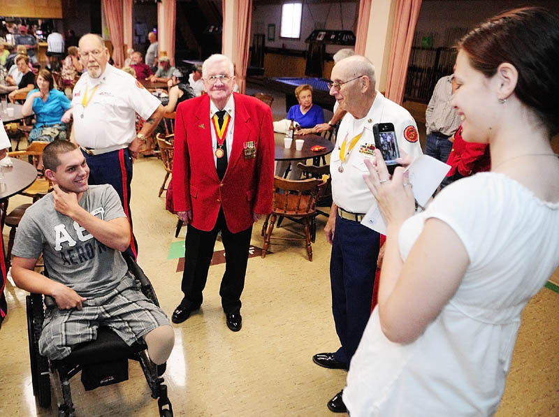 Jeremy Gilley, left, smiles as Rachel Turcotte snaps a photo of him with members of the Marine Corps League Detachment # 599 at a fundraiser held on Wednesday night at Le Club Calumet in Augusta. The older Marines made service rivalry jokes with Army veteran Gilley.