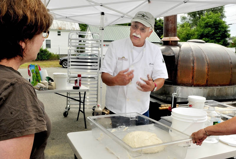 Michael Jubinsky explains the process of working with dough to Lisa Dellmo during the first day of the 2012 Kneading Conference in Skowhegan on Thursday.