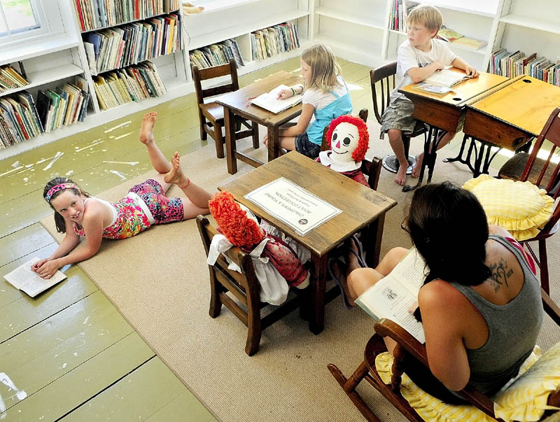 Norah Davidson, left, Reece McGlew, Wes McGlew and their nanny, Amelia Jackson, far right, read books in the children's room on Thursday afternoon at the Albert Church Brown Memorial Library in China Village.